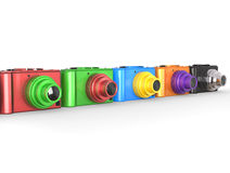 Row of colorful modern digital cameras with different colored lenses Royalty Free Stock Images