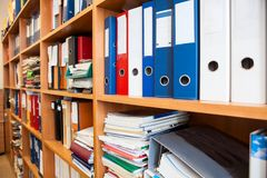 Row of colorful office folders with blank white labels on shelf Royalty Free Stock Photos
