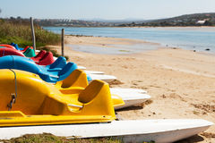 Row of colorful paddleboats next to lagoon Stock Photos