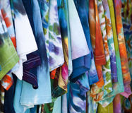 Row of colorful patterned T-shirts hanging up. Close-up of patterned cotton t-shirts hanging on a rack Stock Photos
