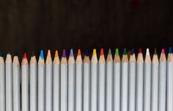 Row of colorful pencils on black background. Drawing concept. Isolated crayons. Rainbow of colored pencils. Pencils closeup. Royalty Free Stock Photo