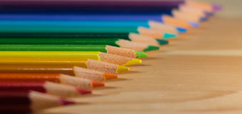 Row of colorful pencils rainbow order on wooden table Royalty Free Stock Photography