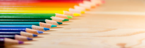 Row of colorful pencils rainbow order on wooden table Royalty Free Stock Image