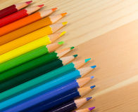 Row of colorful pencils rainbow order on wooden table Royalty Free Stock Photos