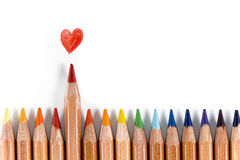 Out of line. Row of colorful pencils. Red pencil out of line and drawn heart above Royalty Free Stock Photo