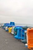 Row of colorful plastic boats on shore. Cloudy sky. Brittany. Royalty Free Stock Photography