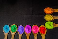 A row of colorful powder colors on wooden spoon in black background. With copy space stock photo