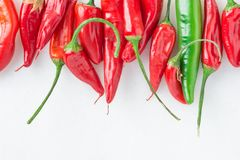 Row of Colorful Red and Green Hot Spicy Chili Peppers on White Marble Stone Background. Upper Border. Food Poster. Mexican Cuisine. Row of Colorful Red and Green stock images