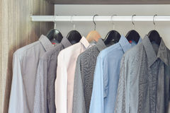 Row of colorful shirts hanging in wardrobe. Row of colorful shirts hanging in wooden wardrobe Royalty Free Stock Photos