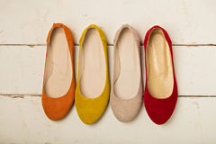 Row of colorful shoes ballerinas on a white wooden background. Stock Photo