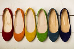 Row of colorful shoes ballerinas on a white wooden background. Royalty Free Stock Photos