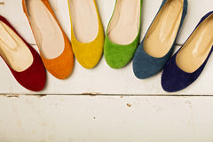 Row of colorful shoes ballerinas on a white wooden background. Stock Photos