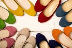 Row of colorful shoes ballerinas on a white wooden background. Stock Image