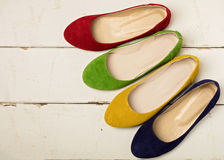 Row of colorful shoes ballerinas on a white wooden background. Royalty Free Stock Images