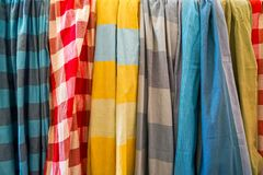 Row of colorful soft cotton fabric scarfs in plain and checker pattern selling in local shop. Thailand Royalty Free Stock Photography