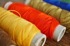 Row of colorful spools with yellow, brown, green, red and blue threads Royalty Free Stock Photo