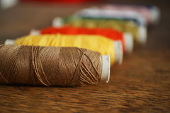 Row of colorful spools with yellow, brown, green, red and blue threads Stock Images