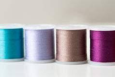 Row of colorful thread spools on table Royalty Free Stock Images