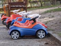 Row of colorful toy cars for kids in a playground. Or parked all neatly parked against a kerb alongside a wooden bench Royalty Free Stock Photos
