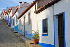 A row of colorful and traditional houses along a steep cobbled street inside Odeceixe near Aljezur, Costa Vicentina, Algarve royalty free stock photography