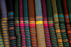 Row of colorful traditional strip pattern fabric textile rolls in local shop Stock Images