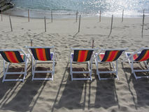 Row of colorful wooden chairs at Marina di Pisa sand beach . Tuscany, Italy Royalty Free Stock Photo