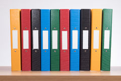 Row of coloured office document folders on shelf Stock Photography