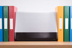 Row of coloured office folders and computer laptop. A computer laptop amongst a row of multicoloured office document folders on a timber desk with white royalty free stock photos