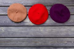 Row of colourful berete hats. Wooden desk surface background Stock Photography