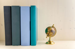 Row of Colourful Books and a Small Vintage Globe. Boooks with Blank Cover and a Globe on a Wooden Background royalty free stock photography