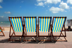Row of colourful deckchairs on Weymouth beach. Row of blue and yellow striped deck chairs on the promenade next to Weymouth beach in Dorset Royalty Free Stock Image