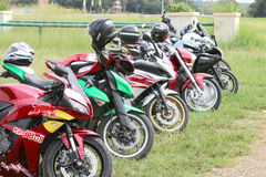Row of colourful parked motorbikes on green grass. Rustenburg, South Africa - March 3, 2017: Row of colourful parked motorbikes on green grass at Yearly Mass Royalty Free Stock Photo