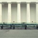 Row of columns and empty benches Stock Photo