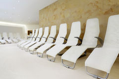 Row of comfortable seats in room for waiting. Row of white comfortable seats in empty light room for waiting Stock Photography