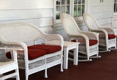 Row of comfy wicker chairs on rustic front porch. Neat and orderly white comfy wicker chairs set on rustic front porch of home, inviting people to come sit and Stock Photo