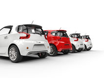 Row of compact cars - red stands out - back perspective view Royalty Free Stock Photo
