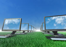 Row of computers in a field of grass.