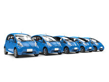 Row of cool blue small modern electric cars Royalty Free Stock Images