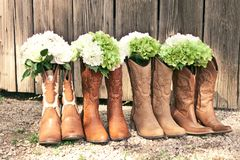 Row of cowboy boots and bouquets at a country theme wedding. Cowboy boots and bouquets are lined up by a grey barn at a country theme wedding royalty free stock photography