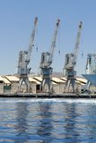 Row of cranes and their reflections in the sea in Eilat harbor. Israel Stock Photo