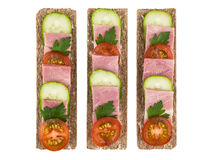 Row of crisp bread with bacon, cucumbers and tomatoes Stock Photography