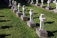 Row of crosses. A row of stone cross shaped tombstones are illuminated by the setting sun stock photography