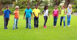 Row of cute pupils racing on the grass. Outside the elementary school stock footage