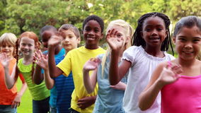 Row of cute pupils waving and smiling at camera. Outside the elementary school stock video