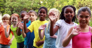 Row of cute pupils waving and smiling at camera. Outside the elementary school stock video footage