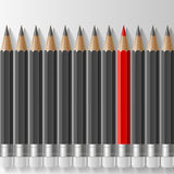 Row of dark grey pencils with one outstanding red Stock Image