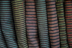 Row of decent traditional strip pattern fabric textile rolls in local shop Stock Images