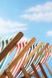 Row of deck chairs on beach Stock Photography