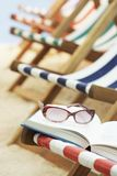 Row of deck chairs on beach book with sunglasses in foreground Royalty Free Stock Photography