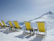 Row of deck chairs overlooking an Alpine peak Royalty Free Stock Images